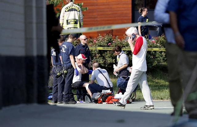 <p>A person is treated by emergency workers as members of the Republican congressional baseball team look on following a shooting in Alexandria, Va, June 14, 2017. (Photo: Shawn Thew/EPA) </p>