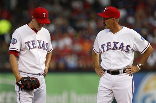 Texas Rangers starting pitcher Derek Holland, left, gets a visit to the mound from pitching coach Mike Maddux, right, in the second inning of baseball game against the Seattle Mariners, Wednesday, May 30, 2012, in Arlington, Texas. Holland was pulled in the second inning with two outs. (AP Photo/Tony Gutierrez)