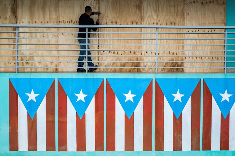 A man finishes boarding up a restaurant at the Naguabo Malecon in Naguabo, Puerto Rico, on Wednesday. (Photo: Dennis M. Rivera Pichardo for HuffPost)