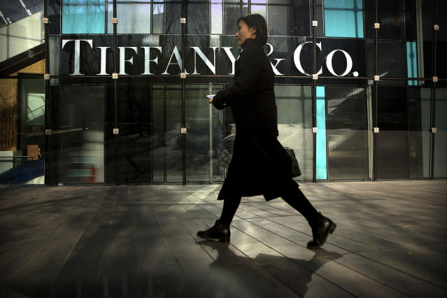 In this Thursday, Nov. 29, 2018, photo, a woman walks past a Tiffany & Co. store at a shopping mall in Beijing. The designer boutiques of Manhattan and Paris are feeling the chill of a Chinese economic slowdown that has hammered automakers and other industries. That is jolting brands such as Louis Vuitton and Burberry that increasingly rely on Chinese customers who spend $90 billion a year on jewelry, clothes and other high-end goods. The industry already is facing pressure to keep up as China's big spenders shift to buying more at the spreading networks of luxury outlets in their own country. (AP Photo/Mark Schiefelbein)