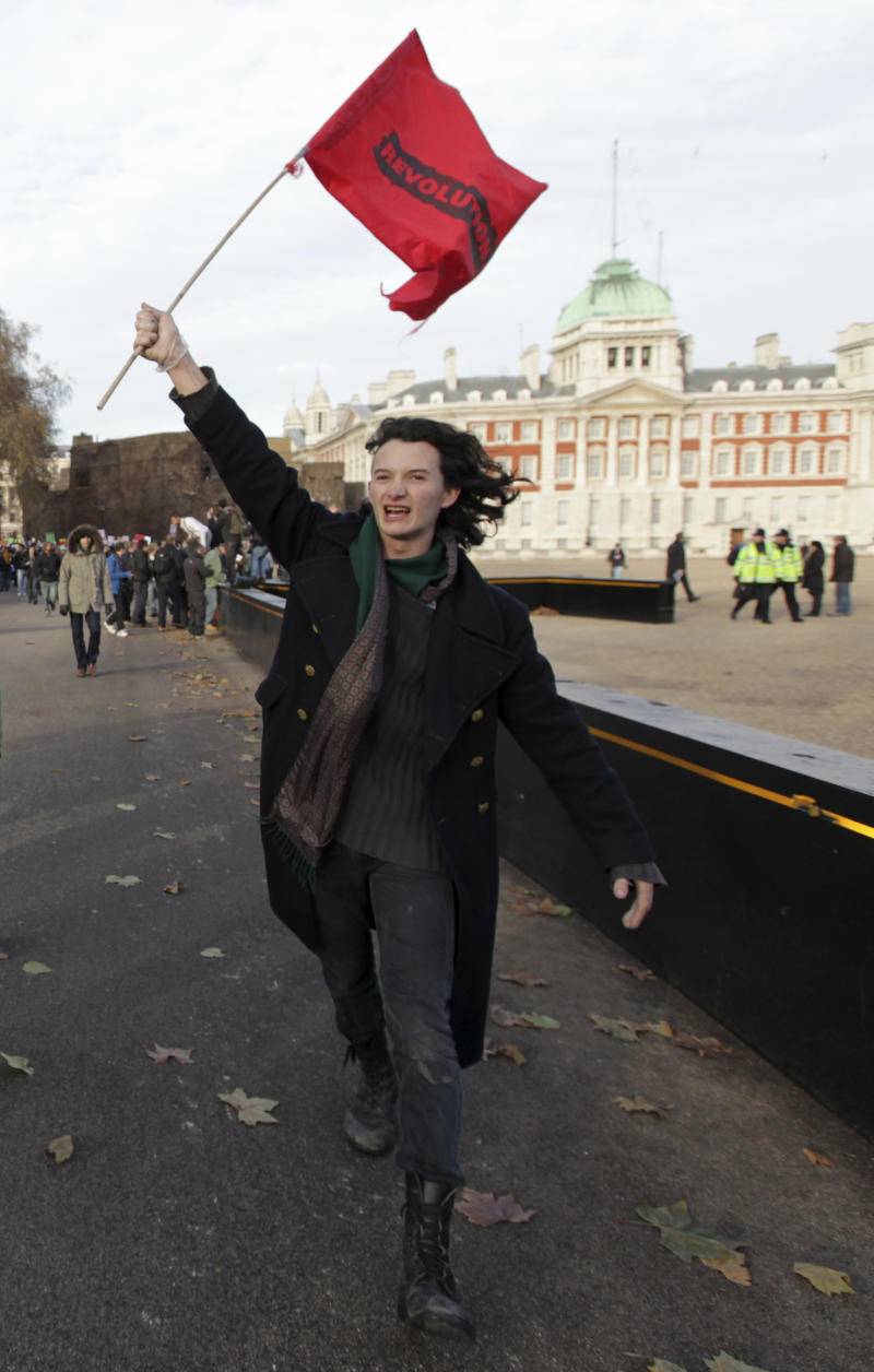 In this Thursday Dec. 9, 2010 photo, Charlie Gilmour, the son of Pink Floyd guitarist David Gilmour, holds a flag with the word 'revolution' on it as he marches along Horse Guards Road, as Horse Guards Parade can been on the right, during a demonstration in central London against government plans to triple tuition fees. Charlie Gilmour has issued a public apology for climbing on top of one of Britain's most important war memorials and trying to rig a British flag during the violent student protests against rising university fees. He added in a statement Friday Dec. 10, 2010 that he was ashamed for his 'moment of idiocy' and he did not realize the Cenotaph in central London commemorates Britain's war dead. (AP Photo/Matt Dunham)