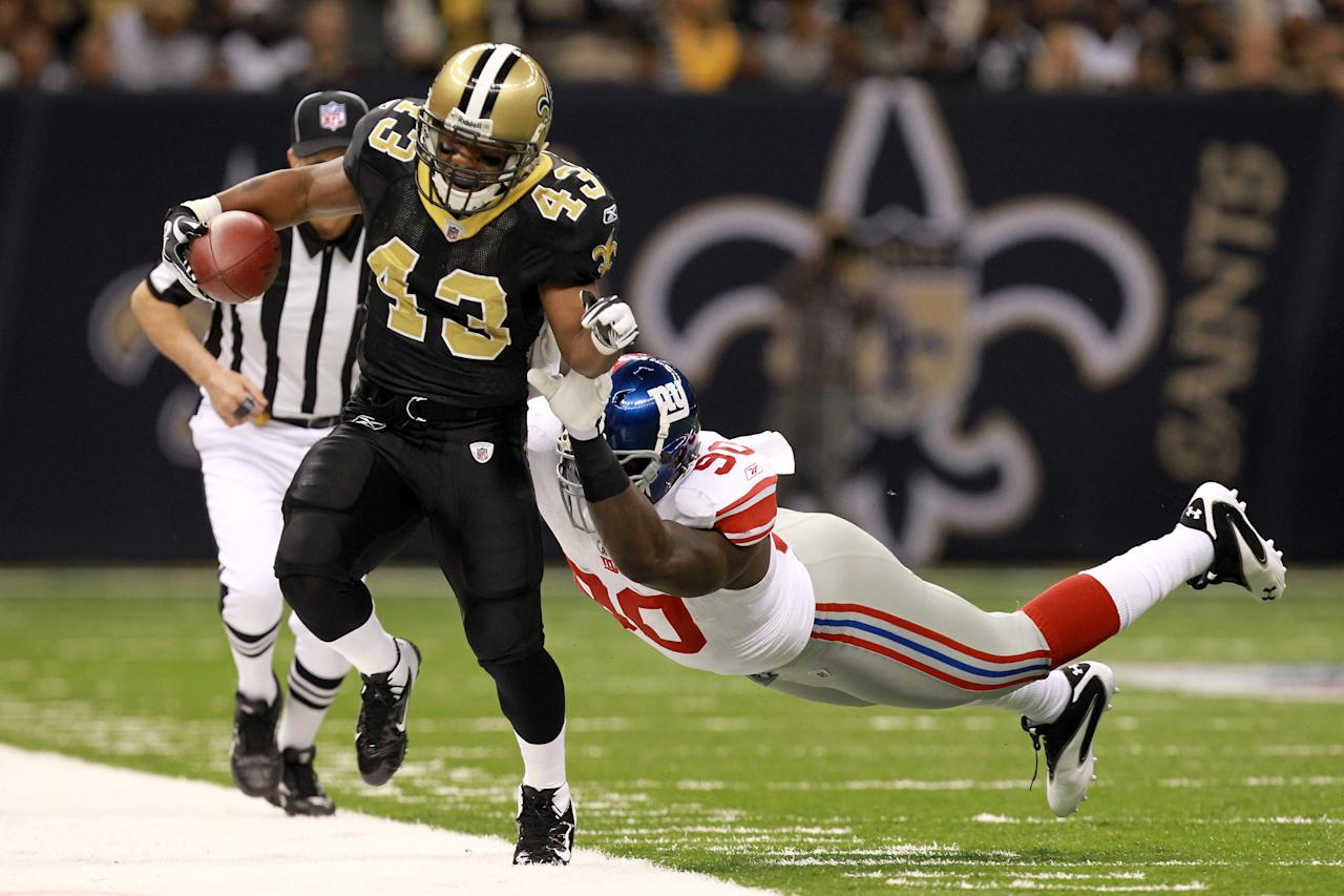 NEW ORLEANS, LA - NOVEMBER 28:  Running back  Darren Sproles #43 of the New Orleans Saints is pushed out of bounds by defensive end Jason Pierre-Paul #90 of the New York Giants after a six-yard gain in the first quarter at Mercedes-Benz Superdome on November 28, 2011 in New Orleans, Louisiana.  (Photo by Ronald Martinez/Getty Images)