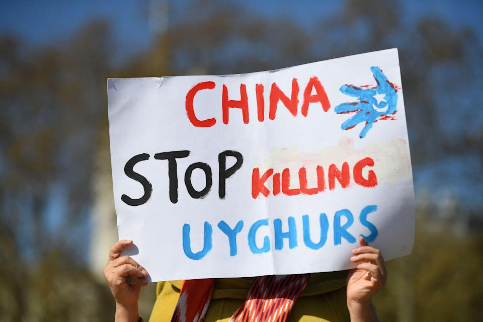 <p>A member of the Uighur community holds a placard as she joins a demonstration to call on the British parliament to vote to recognise alleged persecution of China's Muslim minority people as genocide and crimes against humanity in London on April 22, 2021</p> (Photo by JUSTIN TALLIS/AFP via Getty Images)