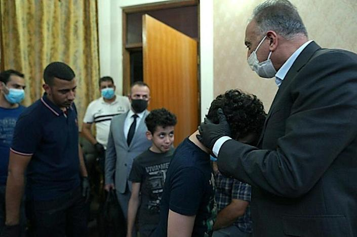 Iraqi Prime Minister Mustafa al-Kadhemi pays his respects to the family of slain scholar and government advisor Hisham al-Hashemi in Baghdad's Zayouna district, hugging his sons (AFP Photo/-)