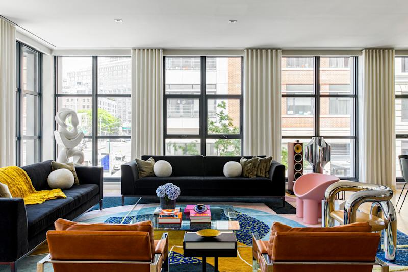 The living room—a big space with high ceilings and floor-to-ceiling windows—features a colorful rug custom made by New York artist Alex Proba. Alex worked with Olivia to develop the home's concept.