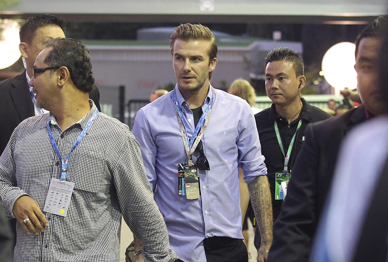 David Beckham arrives at the pit building before the start of the Singapore Formula One Grand Prix on the Marina Bay City Circuit in Singapore, Sunday, Sept. 22, 2013.(AP Photo/Wong Maye-E)