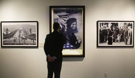 "Assistant curator looks at display of the flag that draped casket of U.S. President John F. Kennedy at the press preview of the special exhibition ""A Nation Remembers"" at John F. Kenn"