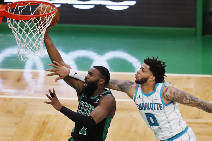 Boston Celtics' Jaylen Brown (7) shoots in front of Charlotte Hornets' Miles Bridges (0) during the first half of an NBA basketball game, Sunday, April 4, 2021, in Boston. (AP Photo/Michael Dwyer)