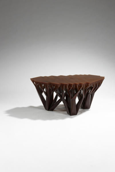 This photo provided by .MGX by Materialise shows a Fractal.MGX coffee table by WertelOberfell, made from a brown epoxy resin from the design division of Belgium-based 3-D printing company, Materialise. It was designed after the growth patterns of trees, whose stems grow into smaller branches until becoming very dense toward the top. A novelty once reserved for science-fiction, 3-D printing has gone mainstream in home decor thanks to cheaper, more accessible technology. (AP Photo/.MGX by Materialise, Copyright StéphaneBriolantParis)