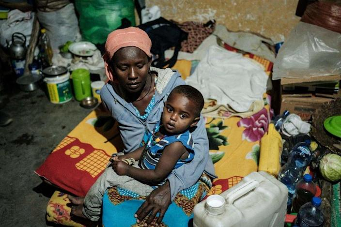A mother, who fled violence in Ethiopia's Tigray region, holds her child in a classroom.