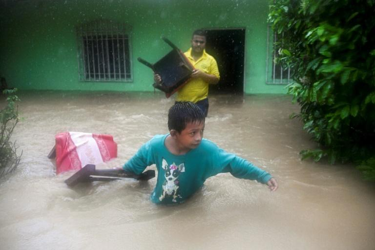 Residents of Puerto Barrios, in northern Guatemala, scramble to save their belongings from flood waters unleashed by storm Eta