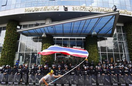 A protester waves a flag in front of police guarding the entrance to the NBT TV station in Bangkok