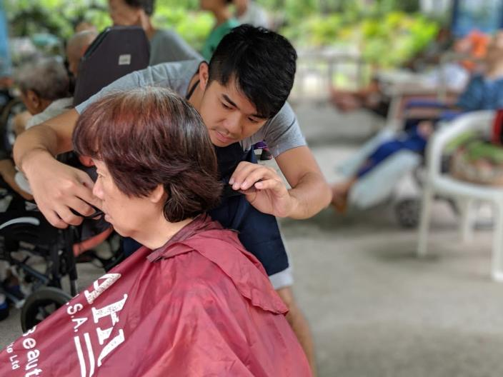 Founder <span>Cai Yinzhou giving a haircut at </span>Green Avenue Home for the Elderly on 19 January, 2019. (PHOTO: Geylang Adventures)