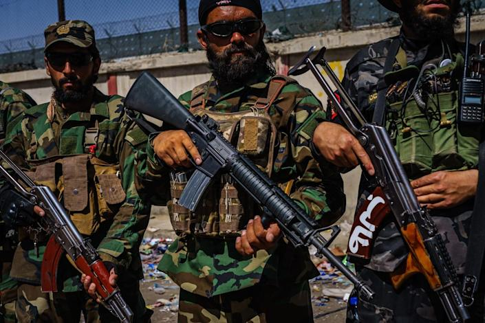 Taliban fighters with rifles stand near a fence