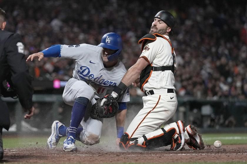 Los Angeles Dodgers' AJ Pollock, left, scores a run as San Francisco Giants catcher Curt Casali drops the ball during the seventh inning of a baseball game Wednesday, July 28, 2021, in San Francisco. (AP Photo/Tony Avelar)