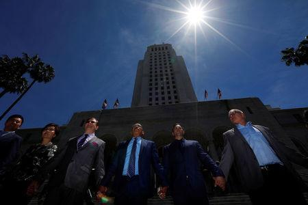 """Members of the Los Angeles City Council and guests, including council president Herb Wesson (C), stand for a moment of unity during the """"Hands Around City Hall"""" event in recognition of the 25th anniversary of the start of the LA riots, in Los Angeles, California April 28, 2017. REUTERS/Patrick T. Fallon"""