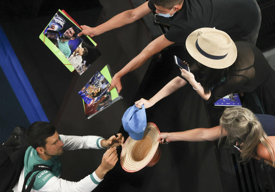 Serbia's Novak Djokovic signs autographs after defeating Russia's Aslan Karatsev in their semifinal match at the Australian Open tennis championship in Melbourne, Australia, Thursday, Feb. 18, 2021.(AP Photo/Hamish Blair)