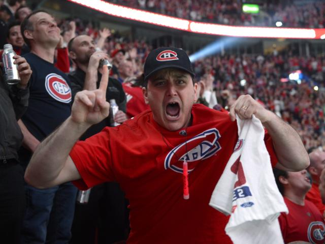 A Montreal Canadiens fan gestures to a camera as fans watch in Montreal the broadcast of the Canadiens' NHL hockey playoff game against the Boston Bruins, Wednesday, May 14, 2014. (AP Photo/The Canadian Press, Ryan Remiorz)