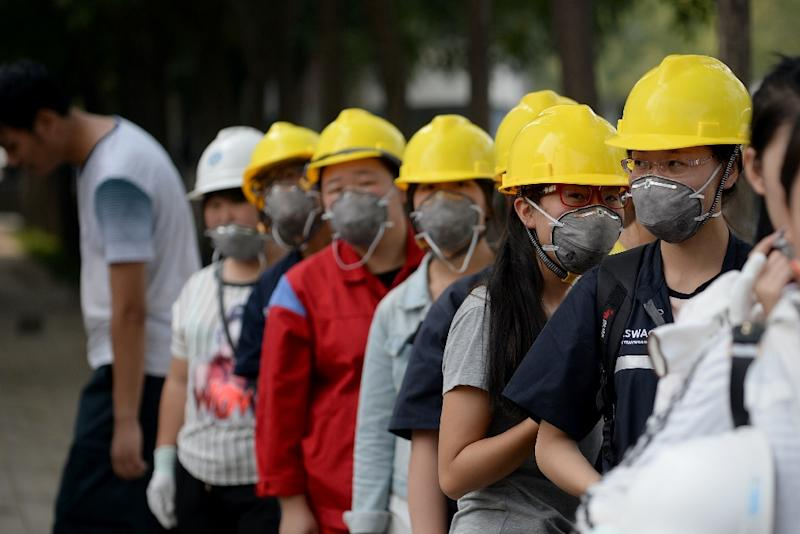 Chinese workers wearing face masks stand outside a factory in Tianjin on August 16, 2015 (AFP Photo/Wang Zhao)