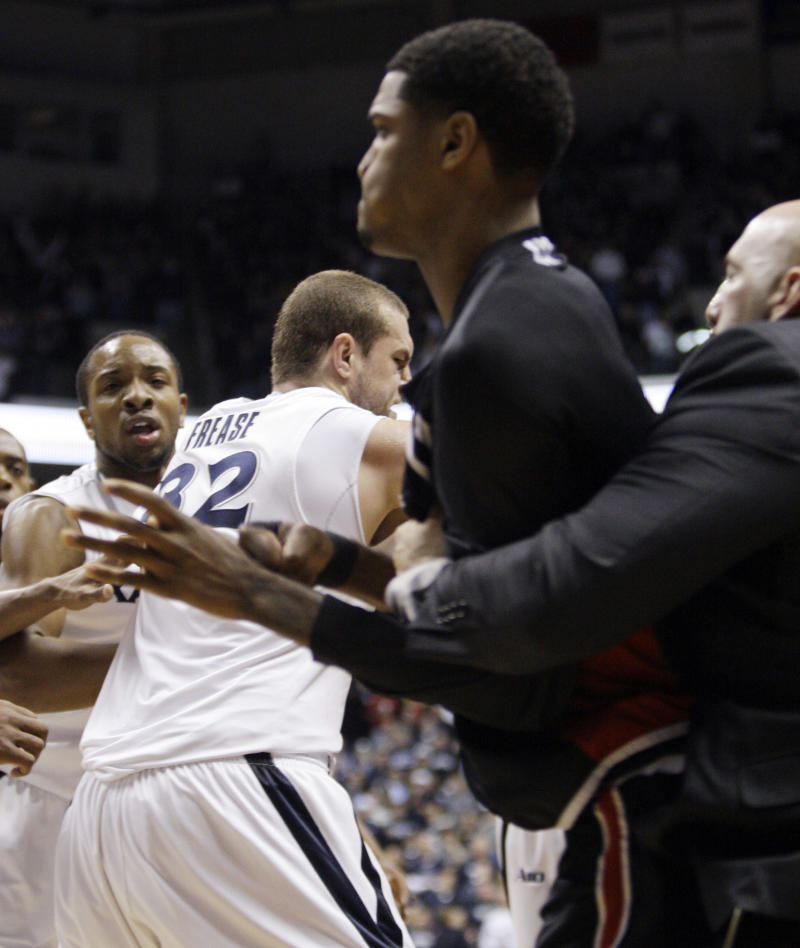 Xavier's Dezmine Wells, left, and center Kenny Frease (32) are held back while a Cincinnati coach holds back a player during a fight at the end of an NCAA college basketball game, Saturday, Dec. 10, 2011, in Cincinnati. Eighth-ranked Xavier defeated crosstown rival Cincinnati 76-53 in a game that was called with 9.4 seconds left when the teams got into a brawl.  (AP Photo/Al Behrman)