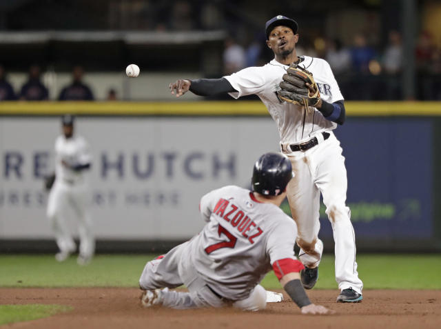 Seattle Mariners second baseman Dee Gordon, right, throws to first after forcing out Boston Red Sox's Christian Vazquez at second base in the seventh inning of a baseball game Thursday, June 14, 2018, in Seattle. Mookie Betts was out at first, ending the top of the inning. (AP Photo/Elaine Thompson)