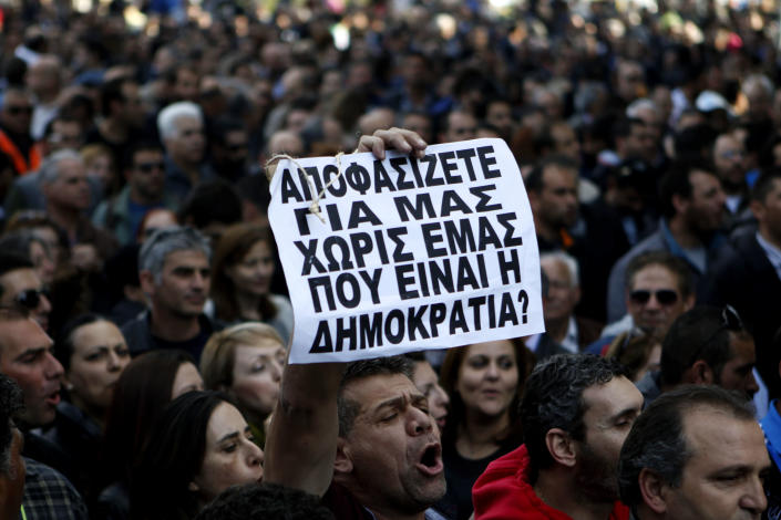 """A protestor holds a banner that reads in Greek """"You decide for us without us, where's the democracy in that?"""" outside of Parliament during a strike to protest government plans to privatize the state-run organizations in capital Nicosia, Cyprus, Thursday, Feb. 27, 2014. Hundreds of protesters have gathered outside Cyprus' parliament to voice opposition against legislation that will pave the way for the privatization of state-owned companies. (AP Photo/Petros Karadjias)"""