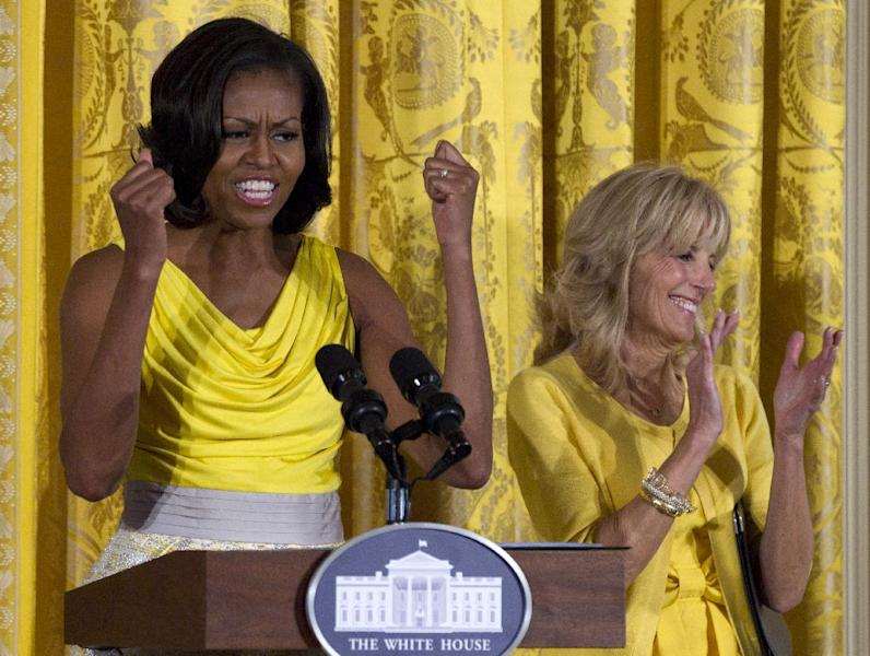 "FILE - In this May 10, 2012, file photo, first lady Michelle Obama, accompanied by Jill Biden speaks at a Joining Forces event in honor of military mothers in the East Room of the White House in Washington. Michelle Obama has a new look, both in person and online, and with the president's re-election, she has four more years as first lady, too. The first lady is trying to figure out what comes next for this self-described ""mom in chief"" who also is a champion of healthier eating, an advocate for military families, a fitness buff and the best-selling author of a book about her White House garden. For certain, she'll press ahead with her well-publicized efforts to reduce childhood obesity and rally the country around its service members. (AP Photo/Carolyn Kaster, File)"