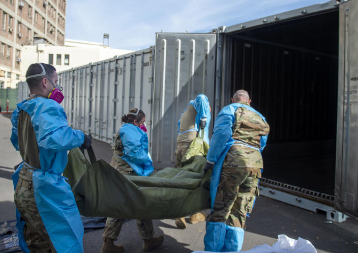 This photo provided by the LA County Dept. of Medical Examiner-Coroner shows National Guard assisting with processing Covid-19 deaths and placing them into temporary storage at LA County Medical Examiner-Coroner Office in Los Angeles on Tuesday, Jan. 12, 2021 in Los Angeles. More than 500 people are dying each day in California because of the coronavirus. The death toll has prompted state officials to send more refrigerated trailers to local governments to act as makeshift morgues. State officials said Friday they have helped distribute 98 refrigerated trailers to help county coroners store dead bodies. (LA County Dept. of Medical Examiner-Coroner via AP)