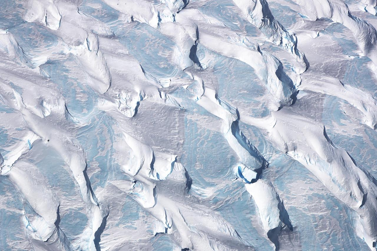 <p>Patterns of ice and blue ice are seen from NASA's Operation IceBridge research aircraft, in the Antarctic Peninsula region on Oct. 31, 2017, above Antarctica. (Photo: Mario Tama/Getty Images) </p>
