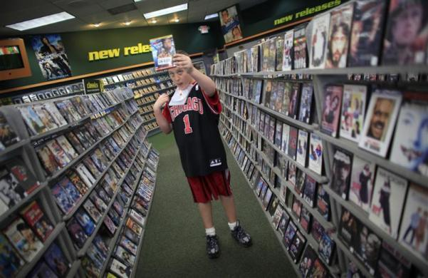 Parker Roos, who suffers from Fragile X, holds up a video as he asks his mother Holly for permission to rent it at a video store in Canton, Illinois, April 4, 2012.