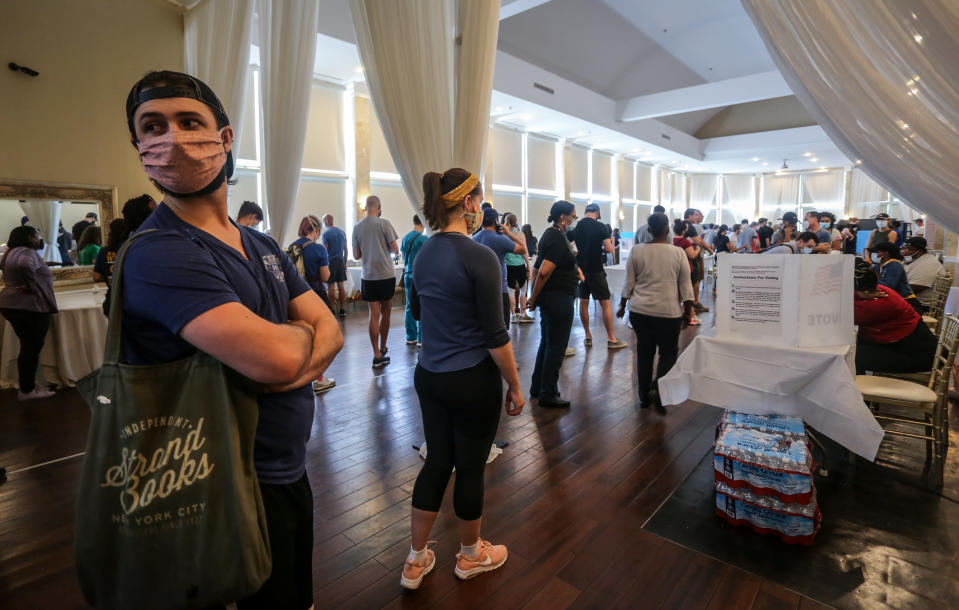 Voters wait in line to cast their ballots in the state's primary election at a polling place, Tuesday, June 9, 2020, in Atlanta, Ga. Some voting machines went dark and voters were left standing in long lines in humid weather as the waiting game played out. (AP Photo/Ron Harris)