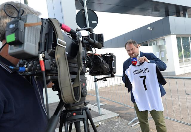 A TV reporter holds a Juventus' jersey as he talks of the transfer of Cristiano Ronaldo to Juventus in Turin, Italy July 10, 2018. REUTERS/Massimo Pinca