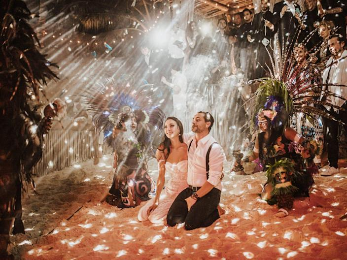 A bride and groom kneel in the sand as dancers perform for them under sparkling lights.