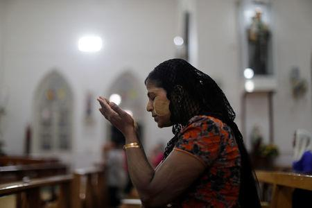 A Catholic woman prays at St. Anthony church at the eve of the mass of Pope Francis in Yangon, Myanmar November 28, 2017. REUTERS/Jorge Silva