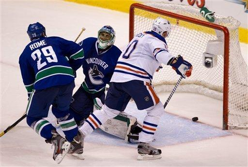 Edmonton Oilers' Shawn Horcoff, right, watches a shot from teammate Taylor Hall, not pictured, enter the net for the tying goal past Vancouver Canucks' goalie Roberto Luongo, center, as Aaron Rome, left, looks on during the third period of an NHL hockey game in Vancouver, British Columbia on Tuesday Jan. 24, 2012. (AP Photo/The Canadian Press, Darryl Dyck)