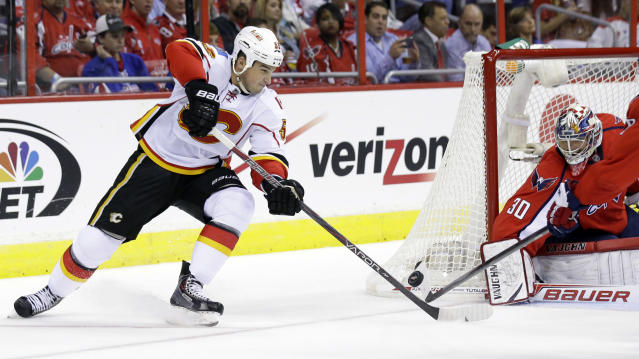 Calgary Flames defenseman Shane O'Brien (55) shoots and has his shot blocked by Washington Capitals goalie Michal Neuvirth (30), from the Czech Republic, in the second period of an NHL hockey game on Thursday, Oct. 3, 2013, in Washington. (AP Photo/Alex Brandon)