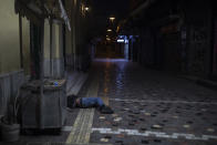 A man sleeps on a street outside shuttered shops in the Monastiraki district of Athens during lockdown measures to prevent the spread of the coronavirus, on Monday, April 27, 2020. (AP Photo/Petros Giannakouris)