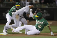 Oakland Athletics' Marcus Semien (10) slides safely next to Chicago White Sox third baseman Yoan Moncada with an RBI triple during the seventh inning of a baseball game Friday, July 12, 2019, in Oakland, Calif. (AP Photo/Ben Margot)