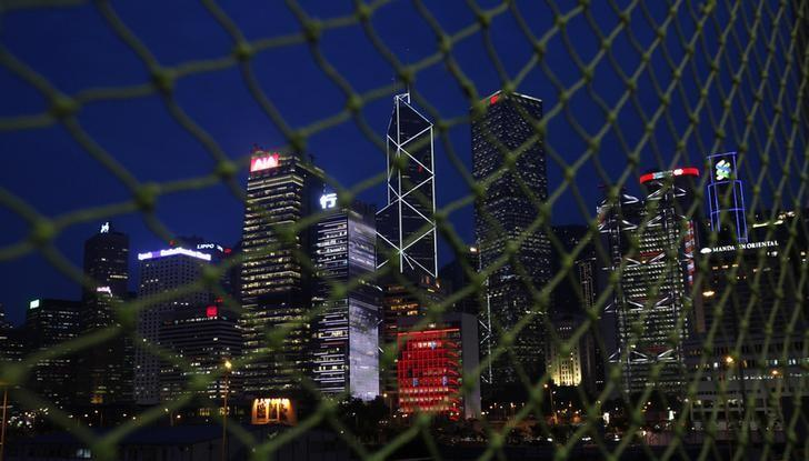 Skyscrapers at Hong Kong's central business district are seen behind a net near a construction site moments after sunset