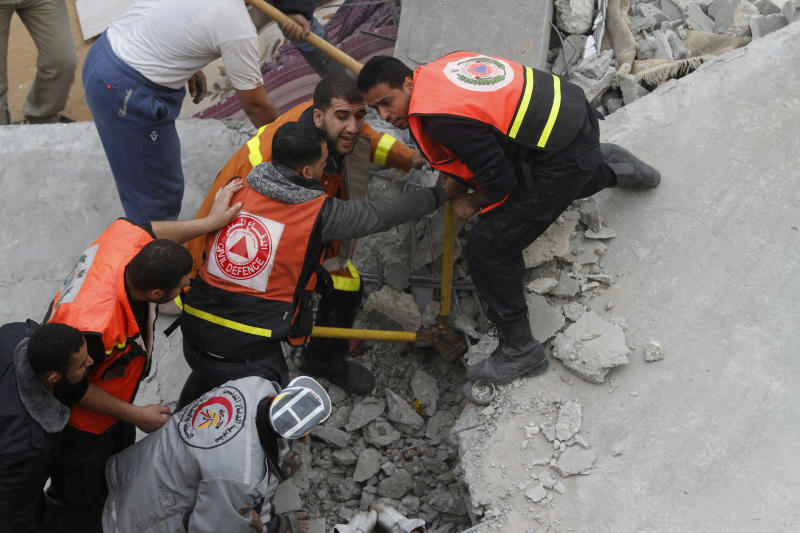Palestinian firefighters work at the scene of an Israeli air strike on a building in the Jebaliya refugee camp in the northern Gaza Strip, Saturday, Nov. 17, 2012. Israel bombarded the Hamas-ruled Gaza Strip with more than 180 airstrikes early Saturday, widening a blistering assault on militant operations to include government and police compounds, militant leaders' residences and a vast network of smuggling tunnels. (AP Photo/Hatem Moussa)