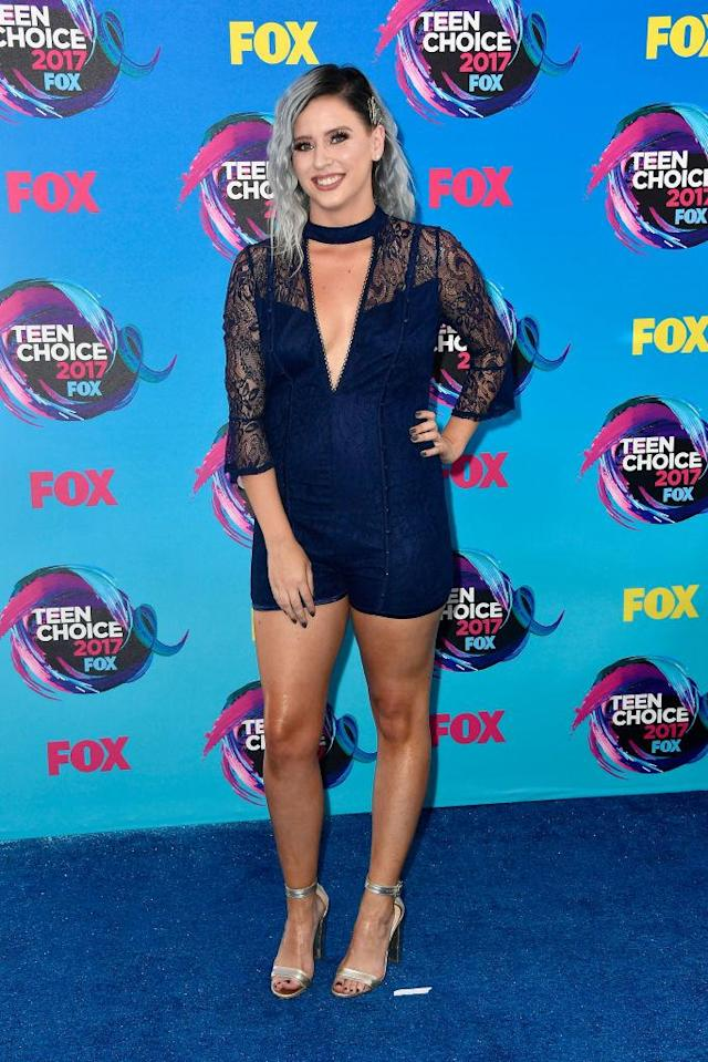 <p>The YouTube star, and <i>Beauty Break</i> host, shines in a navy blue romper with lace details and a plunging neckline. (Photo: Getty Images) </p>