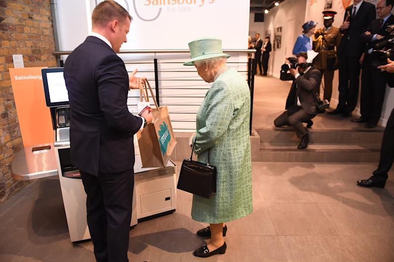 Queen Elizabeth II learning how to use self-checkout inside a pop-up replica of an early Sainsbury's shop in Covent Garden, London, in honor of the store's 150th anniversary, May 2019.