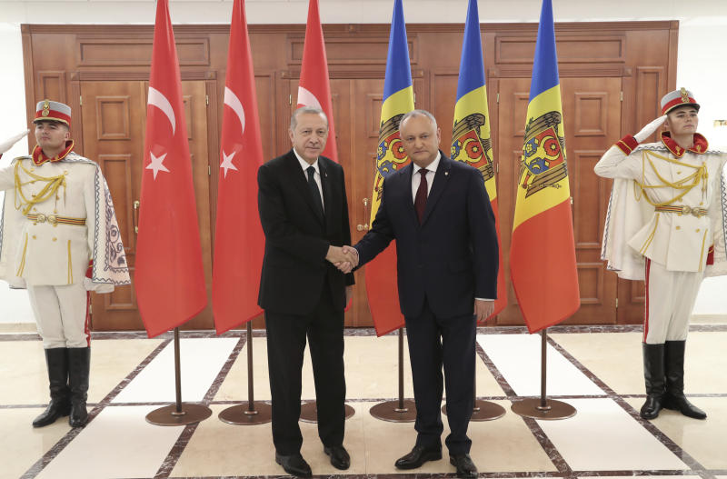 Turkey's President Recep Tayyip Erdogan, left, and Moldova's President Igor Dodon shake hands during a welcome ceremony in Kishinev, Moldova, Wednesday, Oct. 17, 2018. Erdogan is in Moldova for a two-day state visit.( Presidential Press Service via AP, Pool)