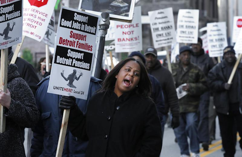 FILE- In this Oct. 23, 2013 file photo, Jalita Shabazz joins protesters during a rally outside The Theodore Levin United States Courthouse in Detroit. The city of Detroit reached tentative agreements to preserve pensions for retired police office and firefighters but cut monthly payments for other former employees, officials said Tuesday, April 15, 2014. (AP Photo/Paul Sancya, File)