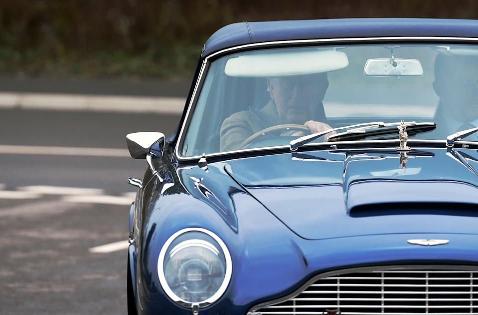 The Prince of Wales driving his Aston Martin DB6 arrives for a visit to the Aston Martin Lagonda factory at St Athan in Barry, Wales.