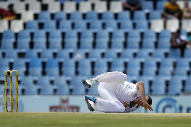 South Africa's falls after making a delivery during the third day of their cricket test match against Australia in Centurion February 14, 2014. REUTERS/Siphiwe Sibeko (SOUTH AFRICA - Tags: SPORT CRICKET)