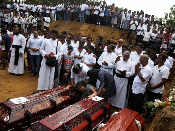 Mass burial of victims at a cemetery near St. Sebastian Church in Negombo, 23 April (Reuters)