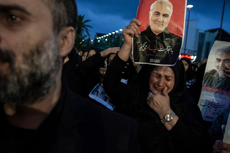 A woman crying while holding a poster of Qasem soleimani. Source: Getty