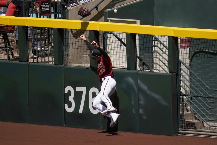 Arizona Diamondbacks right fielder Pavin Smith has his glove pulled off his hand by a home run hit by Cleveland Indians' Jose Ramirez during the first inning of a spring training baseball game Tuesday, March 30, 2021, in Phoenix. (AP Photo/Ross D. Franklin)