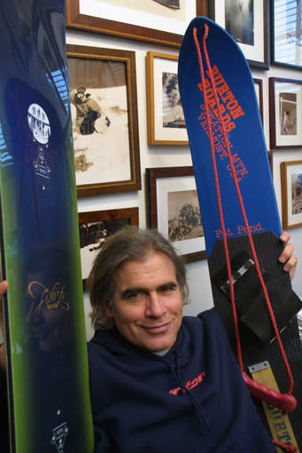 FILE - In this March 8, 2002, file photo, Jake Burton Carpenter, owner of Burton Snowboards, shows an early model, right, and one of the newer snowboards, left, in his office in Burlington, Vt. Carpenter, the innovator who brought the snowboard to the masses and helped turn the sport into a billion-dollar business, has died after a recurring bout with cancer. He was 65. Officials from the company he founded, Burton Snowboards, told The Associated Press of his death Thursday, Nov. 21, 2019. (AP Photo/Alden Pellett, File)